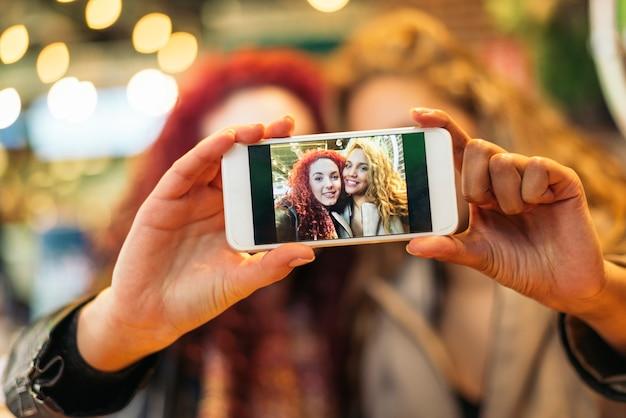 Młodzi przyjaciele robią sobie selfie z telefonem komórkowym w barze restauracyjnym