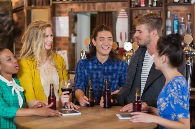 Młodzi przyjaciele rozmawiają, stojąc przy cyfrowych tabletach i butelkach piwa w pubie