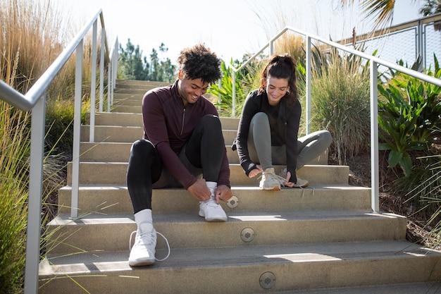 Młodzi przyjaciele siedzą na schodach