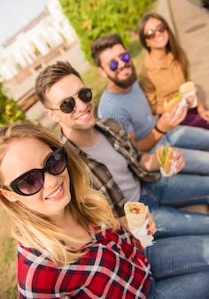 Młodzi przyjaciele siedzą w parku i jedzą fast foody