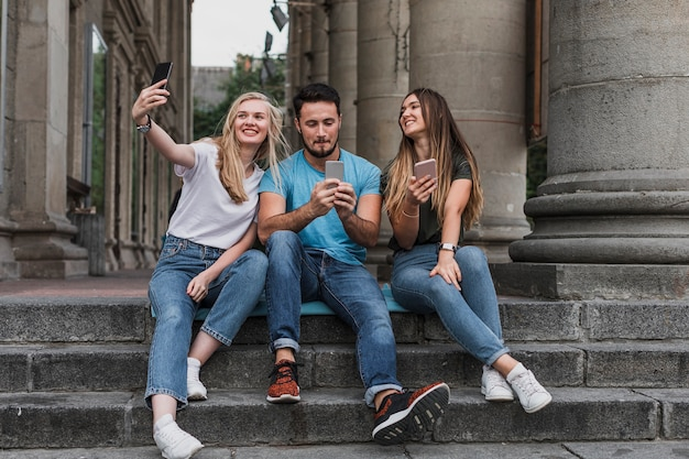 Młodzi przyjaciele siedząc na schodach i biorąc selfie