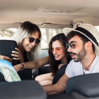 Młodzi przyjaciele siedzi w środku nowoczesnego samochodu patrząc na mapę