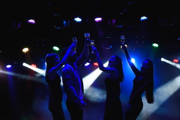 Młodzi przyjaciele tańczy z kieliszkami szampana w ręce. na tle urządzeń oświetleniowych. przyjaciele młodych ludzi tańczą.