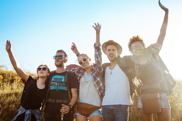 Młodzi przyjaciele uśmiechając się, radując się, patrząc na kamery, stojąc w polu