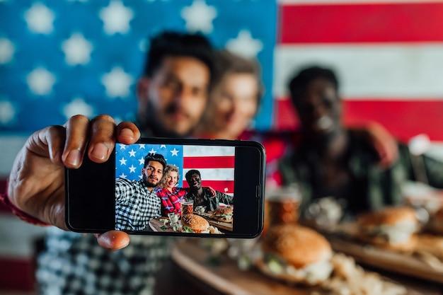 Młodzi przyjaciele w restauracji fast food robią selfie podczas jedzenia hamburgerów i picia piwa