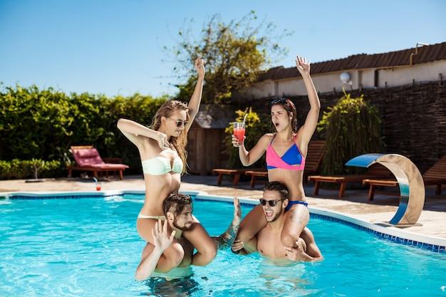Młodzi przyjaciele wesoły, uśmiechając się, śmiejąc się, relaksując się, pływając w basenie