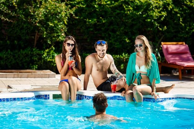 Młodzi przyjaciele wesoły uśmiechnięty, śmiejąc się, relaksujący, pływanie w basenie