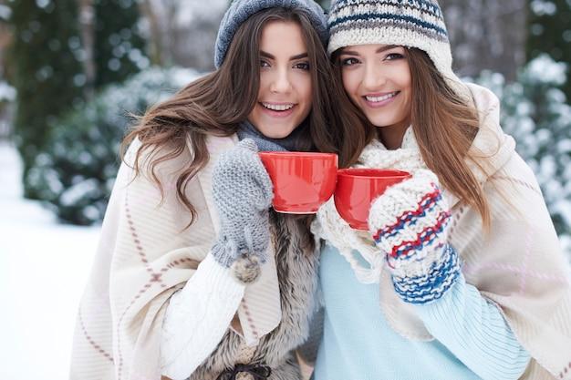 Młodzi przyjaciele z gorącym napojem w zimie