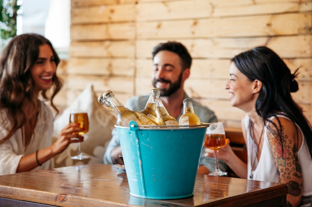 Młodzi przyjaciele z wiadrem piwa