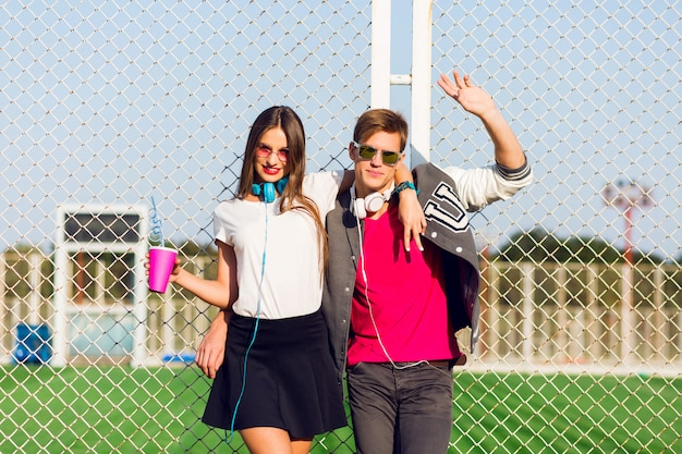 Młodzi przyjaciele zabawni faceci aktywni ludzie bawią się razem, dziewczyna i facet w letnim miejskim stylu casual.
