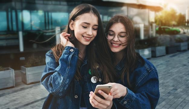Młodzi przyjaciele zabawy z smartphone w dzień wiosny
