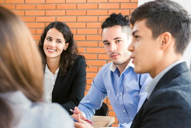 Młodzi przypadkowi ludzie biznesu słucha ich przyjaciela w grupowej dyskusji