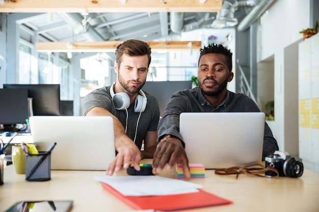 Młodzi przystojni koledzy siedzi w biurowym coworking