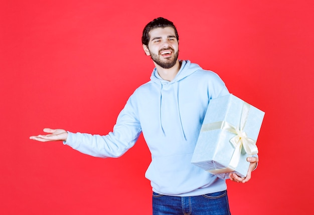 Młodzi przystojni mężczyźni uśmiechający się i trzymający pudełko na prezent