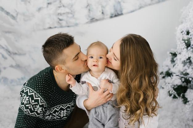 Młodzi rodzice całują pięciomiesięcznego syna w policzki na tle zimowego sztandaru