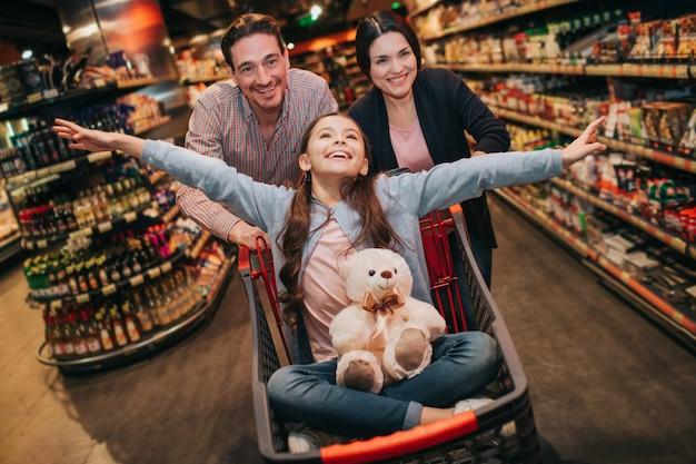 Młodzi rodzice i córka w sklepie spożywczym. figlarna dziewczyna ma misia na kolanach. udaje, że leci. rodzice stoją za i pchają wózek z dziewczyną.