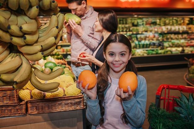 Młodzi rodzice i córka w sklepie spożywczym. mała dziewczynka pozuje na aparat z pomarańczy w rękach. ona się uśmiecha. jej rodzice stoją z tyłu i robią zakupy.