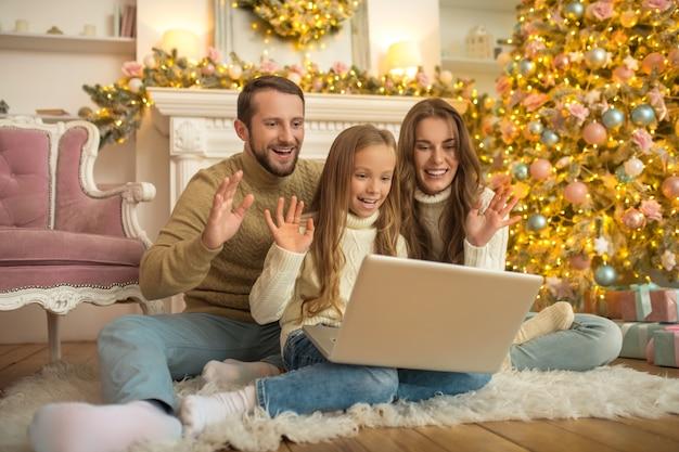 Młodzi rodzice i ich córka rozmawiają przez wideo