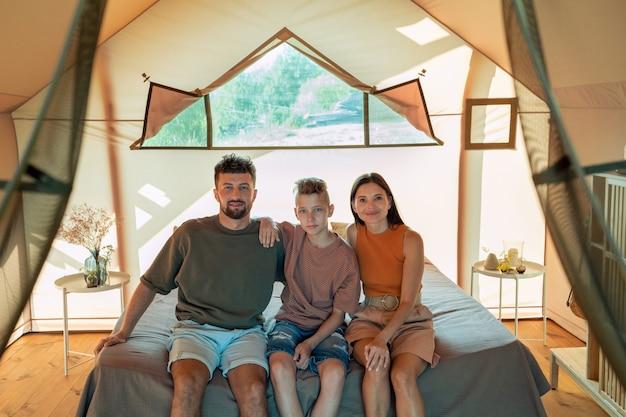 Młodzi rodzice i ich nastoletni syn odpoczywają w domu glampingowym