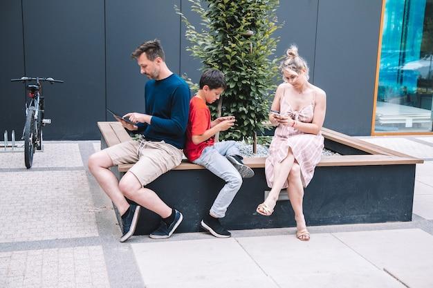 Młodzi rodzice i syn korzystają z technologii bezprzewodowej podczas relaksu na placu miejskim w letni dzień. wysokiej jakości zdjęcie. styl życia