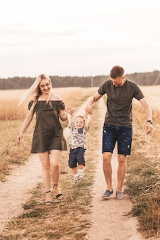 Młodzi rodzice, mama i tata, spacerują latem na łonie natury z małym synem