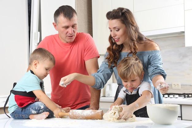 Młodzi rodzice obok małych dzieci, którzy wyrabiają ciasto na kuchennym stole