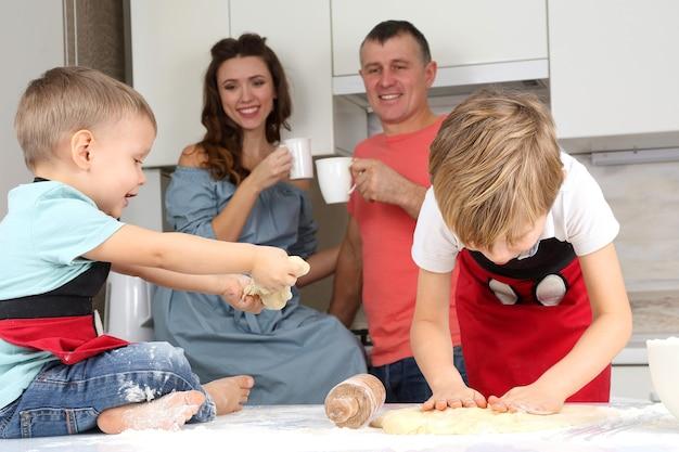 Młodzi rodzice obserwują młodych synów, którzy ugniatają ciasto na kuchennym stole