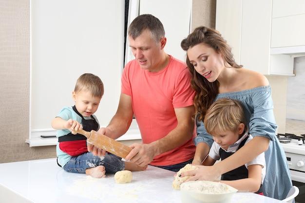 Młodzi rodzice pomagają młodym synom wyrabiać ciasto na kuchennym stole