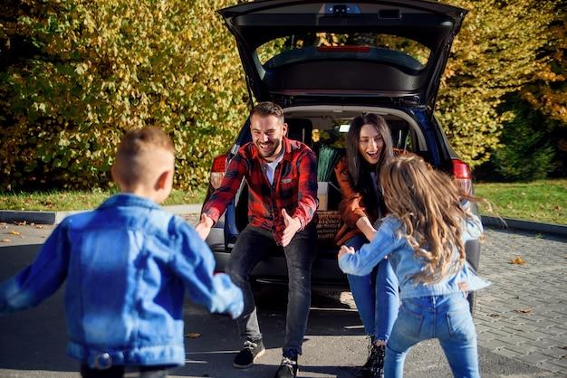 Młodzi rodzice siedzą w bagażniku samochodu i łapią, by uściskać szczęśliwego syna i córkę, którzy do nich podbiegają.