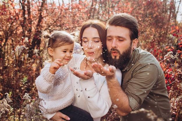 Młodzi rodzice z córką spacerują w jesiennym parku