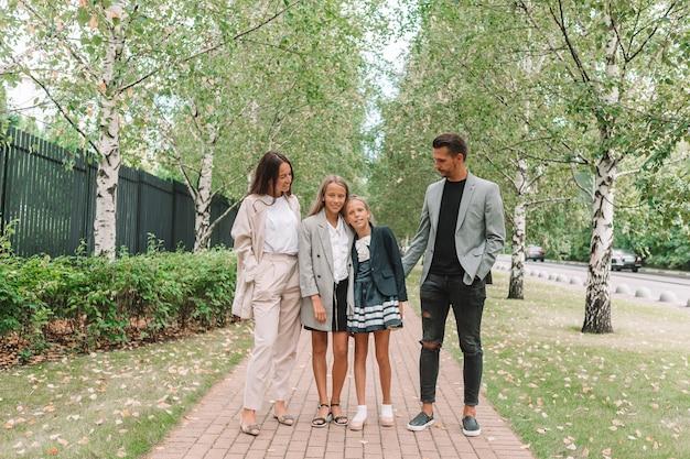 Młodzi rodzice z dziećmi w szkole jesienią. powrót do szkoły