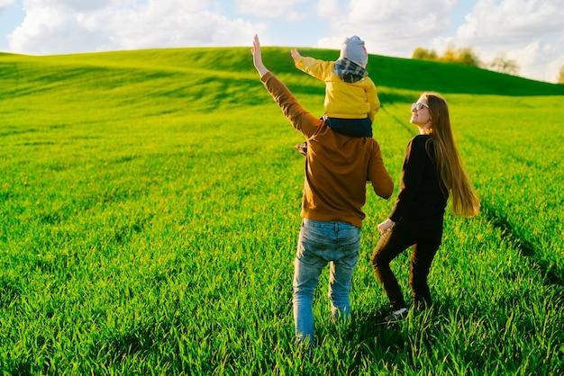 Młodzi rodzice z młodym synem spacerującym po polu o zachodzie słońca w lecie. pojęcie rodziny