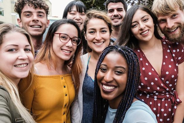 Młodzi, różnorodni ludzie bawią się, robiąc selfie na świeżym powietrzu w mieście – skup się na dziewczynie w okularach