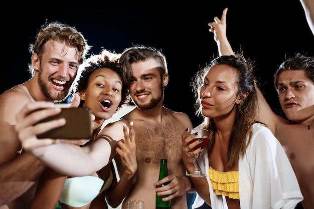 Młodzi rozochoceni przyjaciele uśmiecha się, raduje się, robi selfie, odpoczywa przy przyjęciem