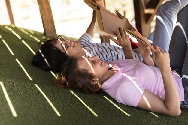 Młodzi rozochoceni ucznie czyta książki kłama na trawie