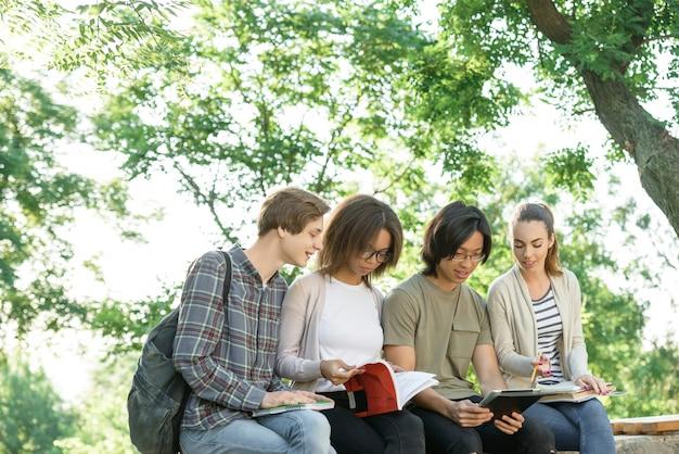 Młodzi rozochoceni ucznie siedzi outdoors i studiuje