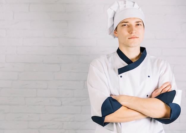 Młodzi samiec kucharza ręk skrzyżowanie na klatce piersiowej