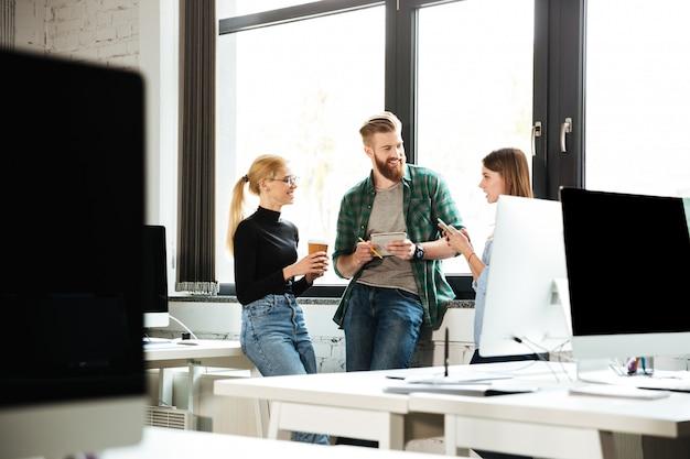 Młodzi skoncentrowani koledzy w biurze rozmawiają ze sobą