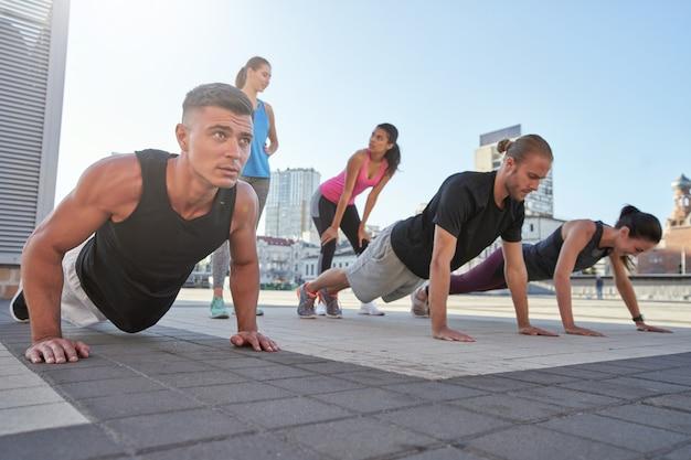 Młodzi sportowcy rasy mieszanej robią pompki na placu miejskim