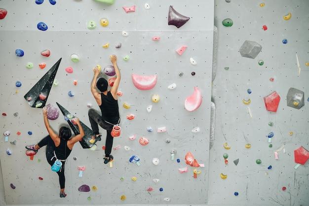 Młodzi sportowcy trenują w pomieszczeniu i wspinają się po ścianie bulderowej, widok z góry