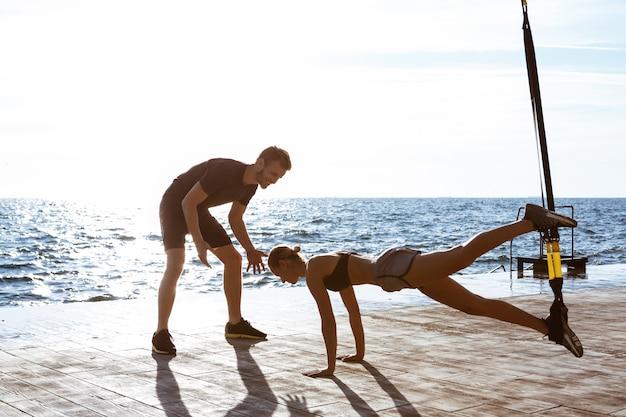 Młodzi sportowi ludzie trenuje z trx blisko morza w ranku.