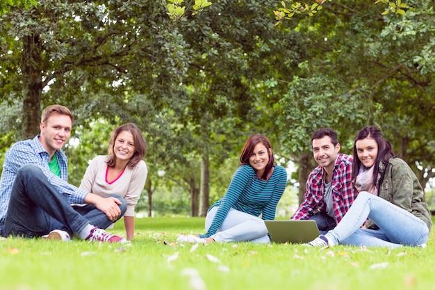 Młodzi studenci collegu używa laptop w parku