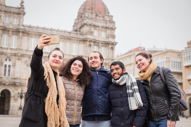 Młodzi studenci erasmusa robią selfie w wielokulturowej grupie w corunna galicia w hiszpanii. wielorasowy styl życia