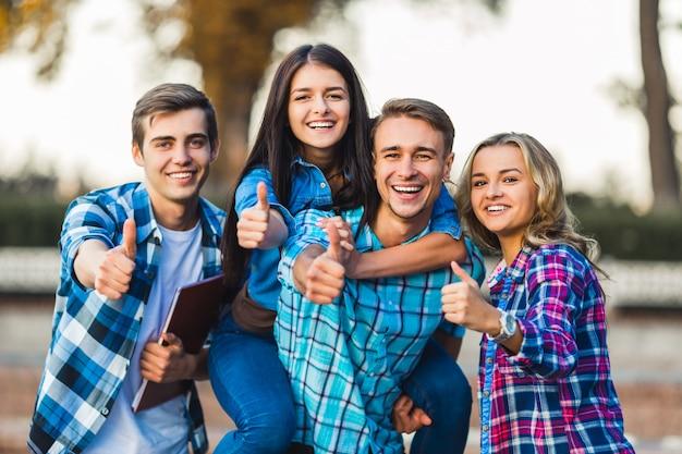 Młodzi studenci pokazują razem kciuki.