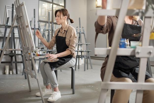 Młodzi studenci profesjonalnego kursu malarstwa z paletami kolorów i pędzlami siedzą przed sztalugami i pracują
