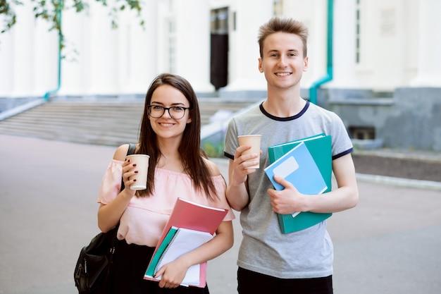 Młodzi studenci z kawą i materiałami do nauki podczas przerwy przed uniwersytetem