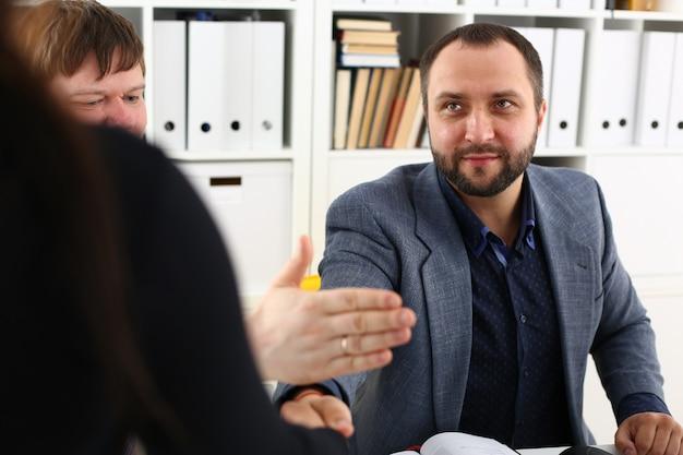 Młodzi szczęśliwi biznesmeni spotykają się w biurze, kłócą się ze sobą, mają różne punkty widzenia