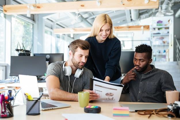 Młodzi szczęśliwi koledzy siedzi w biurowym coworking