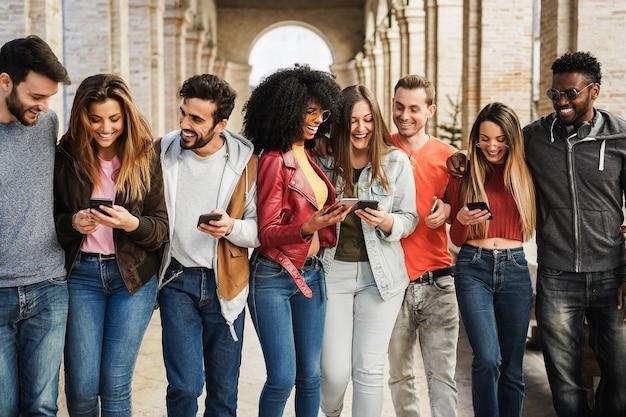 Młodzi szczęśliwi ludzie bawią się razem z aplikacją na telefon komórkowy na świeżym powietrzu w mieście - skup się na twarzach