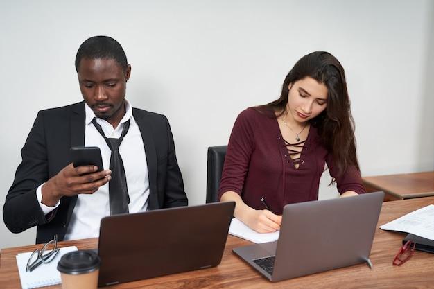 Młodzi szczęśliwi ludzie biznesu współpracuje w nowoczesnym biurze, wieloetniczna praca zespołowa. mężczyzna dzwoni z smartphone